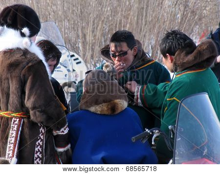 Nadym, Russia - March 18, 2006:  Strangers Nenets Standing And Chatting Near Snowmobiles.