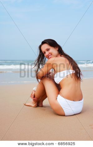 Lively Woman Sitting On The Sand