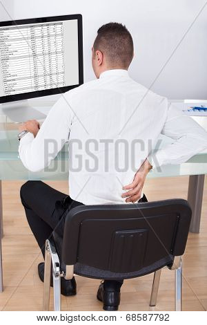 Businessman With Backache Using Computer At Desk