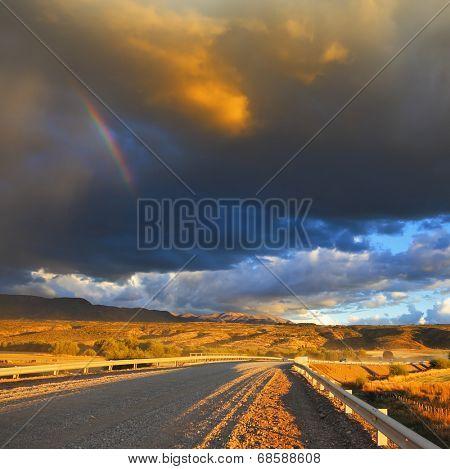Low swirling cloud and flat plain covered in orange sunset. Cloud crosses the rainbow. In the steppe runs a gravel road. Storm over the Pampas