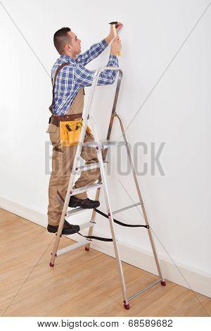 Foreman Hammering Wall With Nail