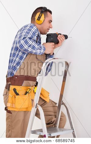 Repairman Drilling Hole In Wall