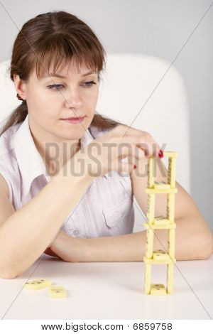 Woman Builds Precarious Tower Of Dominoes