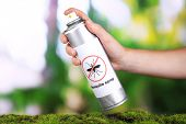 stock photo of mosquito repellent  - Hand holding mosquito spray on nature background - JPG