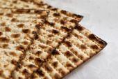 stock photo of matzah  - three jewish passover matzah on white tablecloth - JPG
