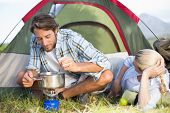 pic of saucepan  - Attractive happy couple cooking on camping stove on a sunny day - JPG