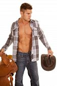 picture of cowboy  - A cowboy holding onto his hat and his sadde with a serious expression - JPG