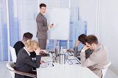 stock photo of boring  - Colleagues getting bored during business presentation given by businessman in office - JPG