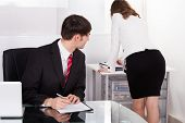 stock photo of pervert  - Young pervert businessman looking at businesswoman working in office - JPG