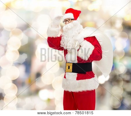 christmas, holidays and people concept - man in costume of santa claus with bag looking far away over lights background