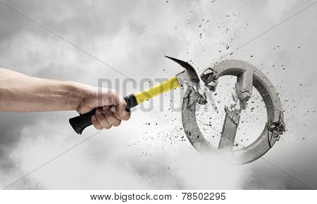 Close up of hammer in human hand breaking stone prohibition mark