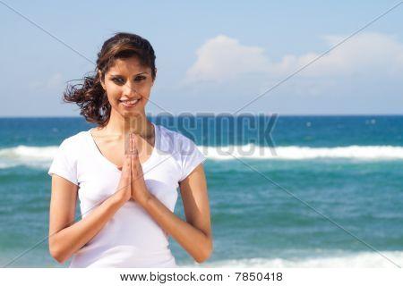 indian woman praying on beach