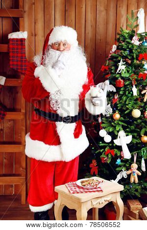 Santa Claus standing near Christmas at home