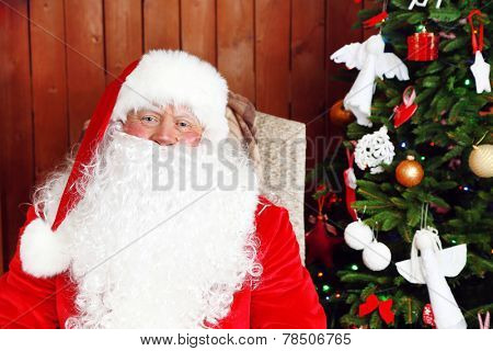 Santa Claus sitting in comfortable rocking chair near Christmas at home