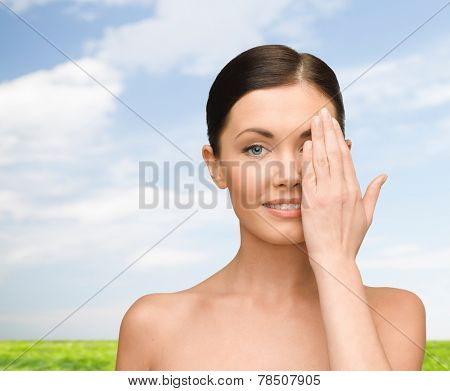 beauty, people and health concept - smiling young woman covering half of face with hand over blue sky and grass background