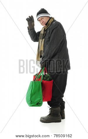 A bundled senior man looking back and waving at the viewer as he carries two shopping bags full of Christmas.  On a white background.