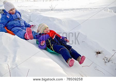 Two Girls Rolling Down A Hill In Snow