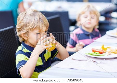 Two Little Kid Boys Having Healthy Breakfast In Hotel Restaurant Or City Cafe