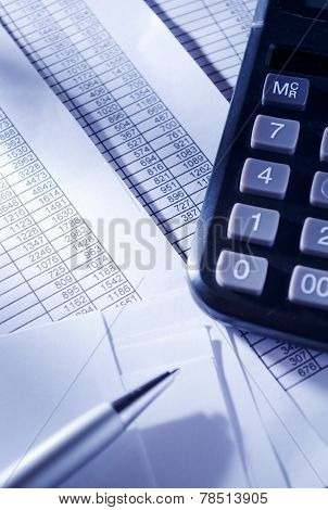 Calculator And Pen On Top Of Invoice Reports