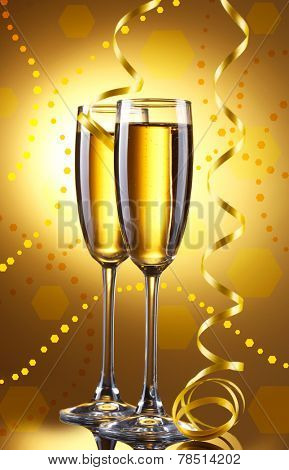 Glasses of champagne with serpentine on bright background