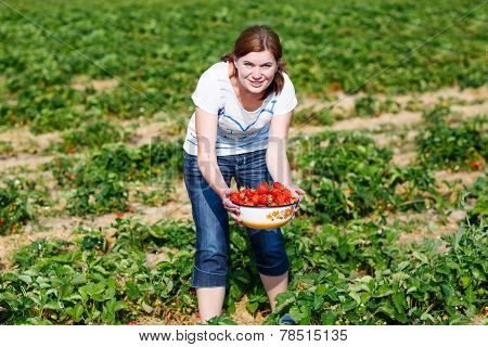 Happy Young Woman On Pick A Berry Farm Picking Strawberries