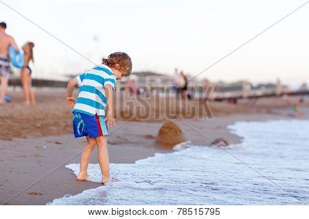 Happy Little Kid Boy Having Fun With Running Through Water In Ocean