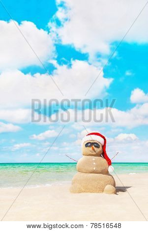 Sandy Snowman In Santa Hat At Beach. Christmas Concept