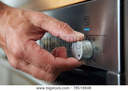Close Up Of Hand Setting Temperature Control On Oven