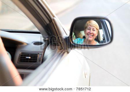 senior woman looking in side mirror