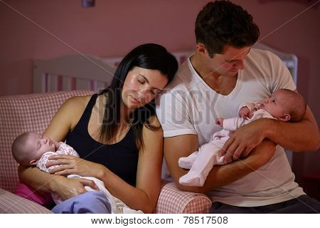 Tired Parents Cuddling Twin Baby Daughters In Nursery