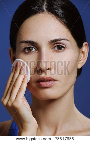 Pretty healthy woman clean skin around the eyes and remove makeup