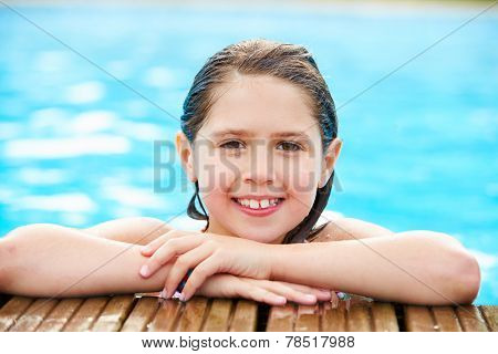 Two Young Girls Jumping Into Swimming Pool Together