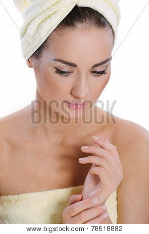 Sweet Young Woman Wrapped In Towel With Fresh Healthy Skin Applying Hand Cream After Bath. Spa Woman