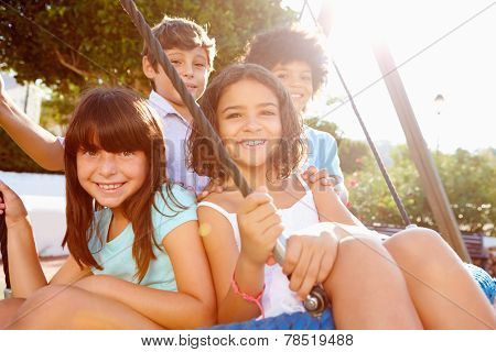 Group Of Children Having Fun On Swing In Playground