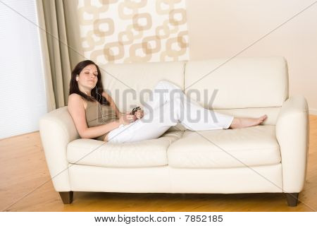 Woman Holding Music Player Listening On Sofa Home