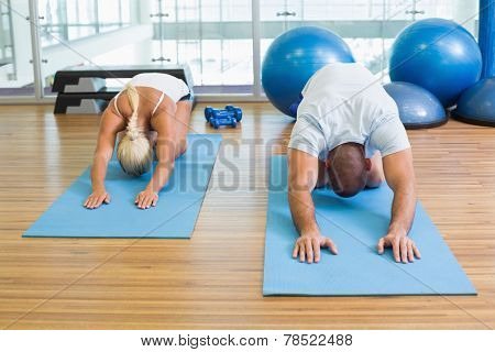 Sporty young couple in bending posture at the fitness studio