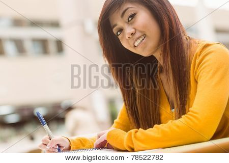 Portrait of female college student doing homework in outdoor canteen