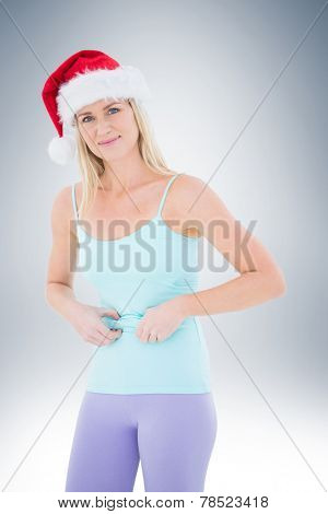 Festive fit blonde pinching her stomach on vignette background