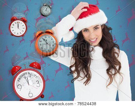 Confused brunette in santa hat against blue and purple reindeer pattern