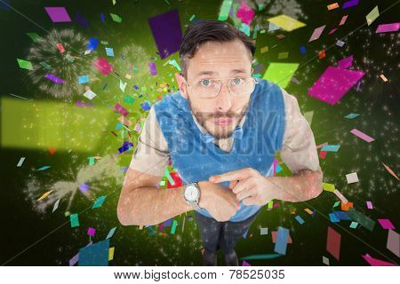 Geeky hipster looking at camera pointing at watch against colourful fireworks exploding on black background