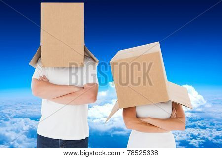 Mature couple wearing boxes over their heads against mountain peak through the clouds