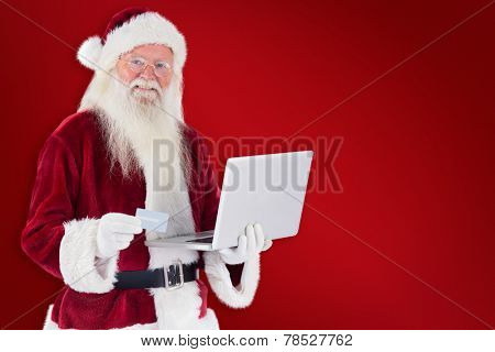 Santa pays with credit card on a laptop against red background