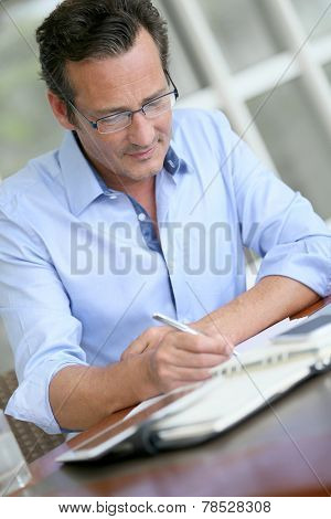 Businessman with eyeglasses writing notes on paper