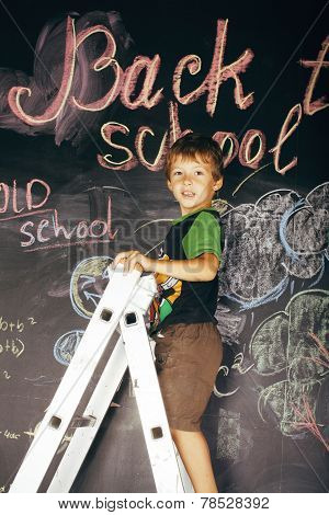 little cute boy at blackboard in classroom, back to school