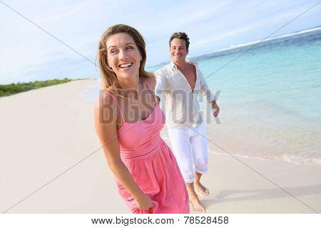 Cheerful couple running on a sandy beach