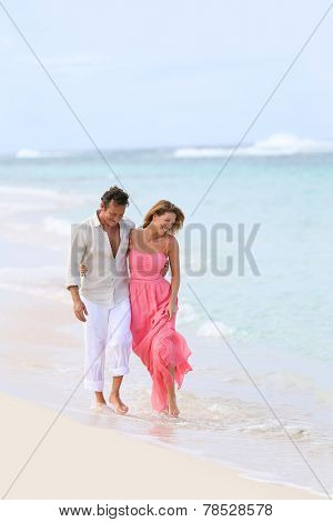 Romantic couple walking on a sandy beach