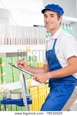 Sales Clerk At Work On A Ladder