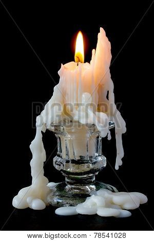 Burning candle in glass candlestick