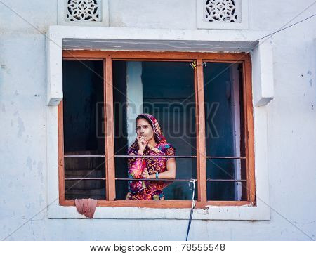 UDAIPUR, INDIA - NOVEMBER 24, 2012: Indian woman in traditional Rajasthani outfit in window. Udaipur in Rajasthan is one of major tourist destinations