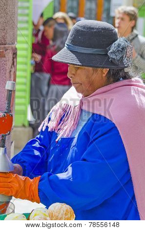 LA PAZ, BOLIVIA, MAY 9, 2014:  Local woman prepares fresh orange juice on street stand